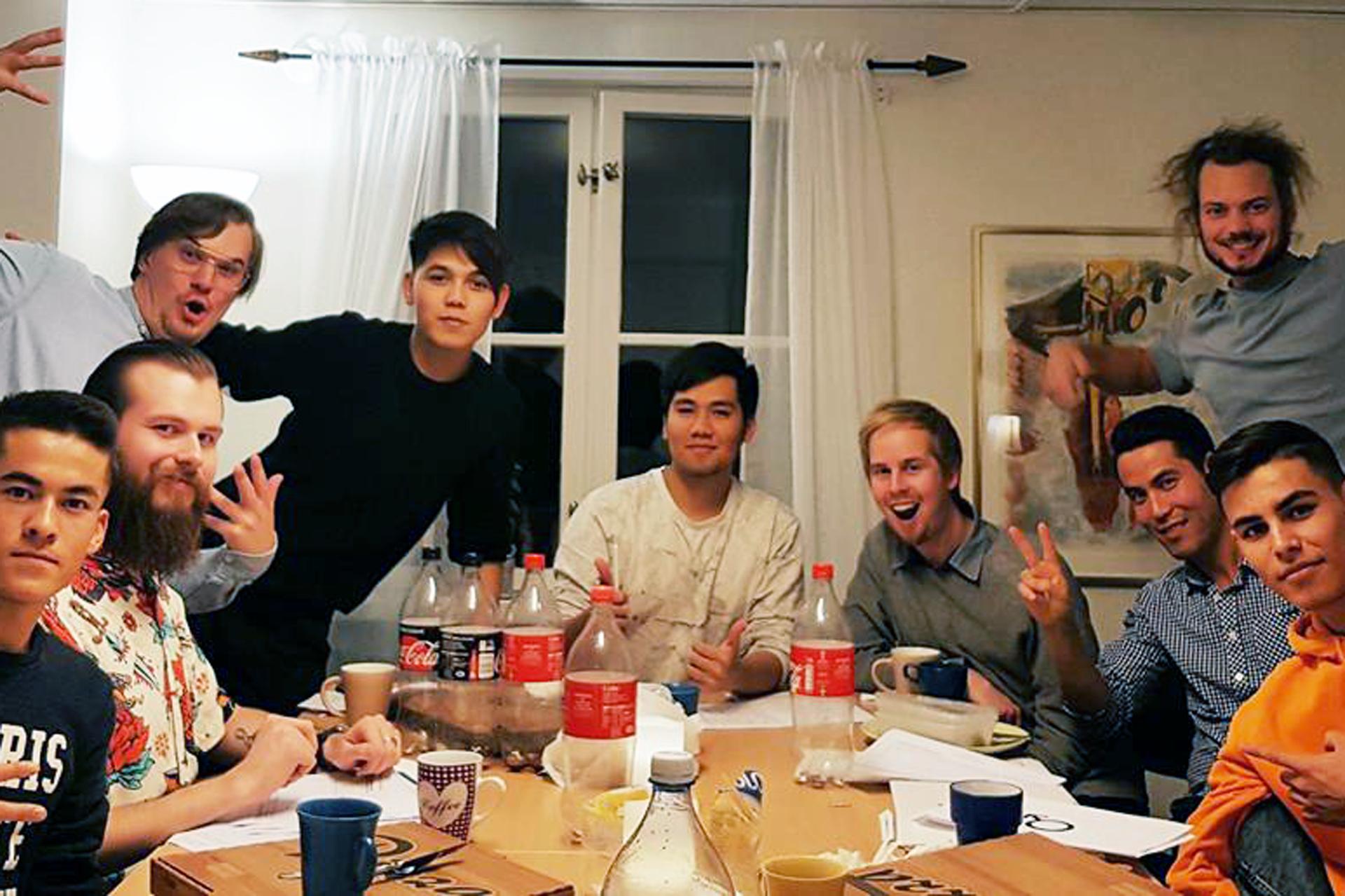 Killmiddag tio unga killar olika ursprung poserar runt matbord